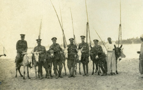 Soliders with donkeys in front of boats on the banks of the Nile river